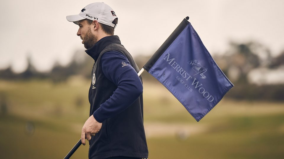 merrist wood golfer holding crown golf flag